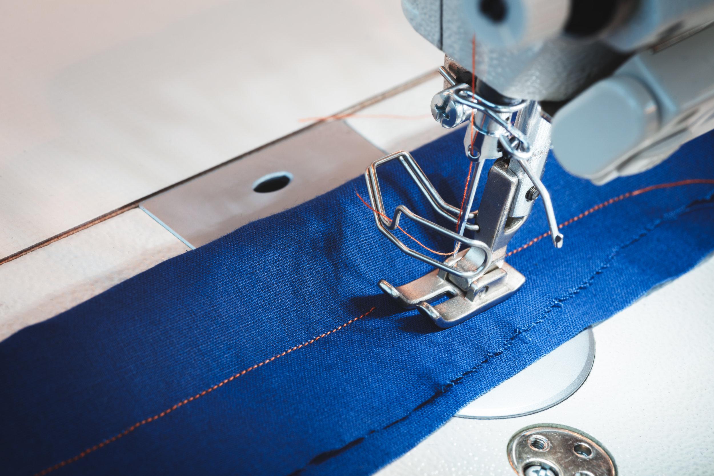 Sewing machine stitching blue fabric