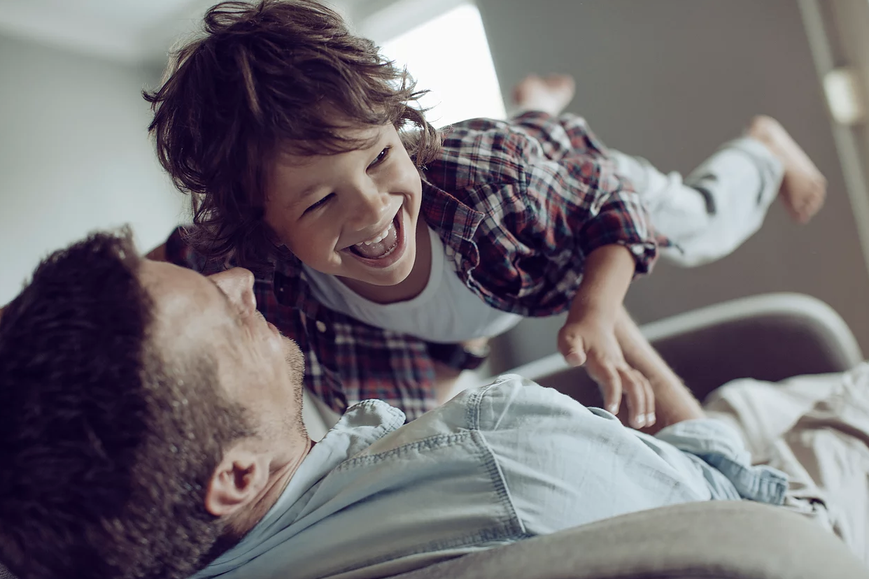 Magic Words Therapy - a father and son playing and smiling.png