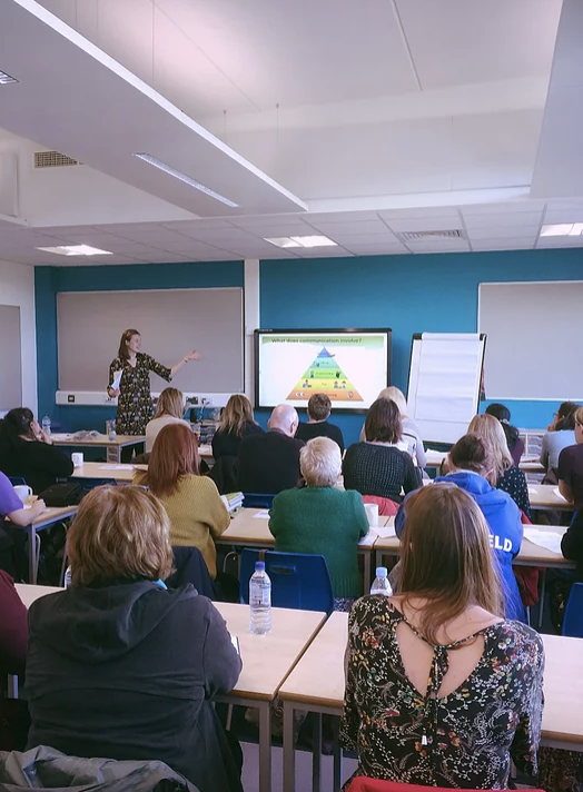 Magic Words Therapy - a photo of a full classroom with a presenter at the front.png