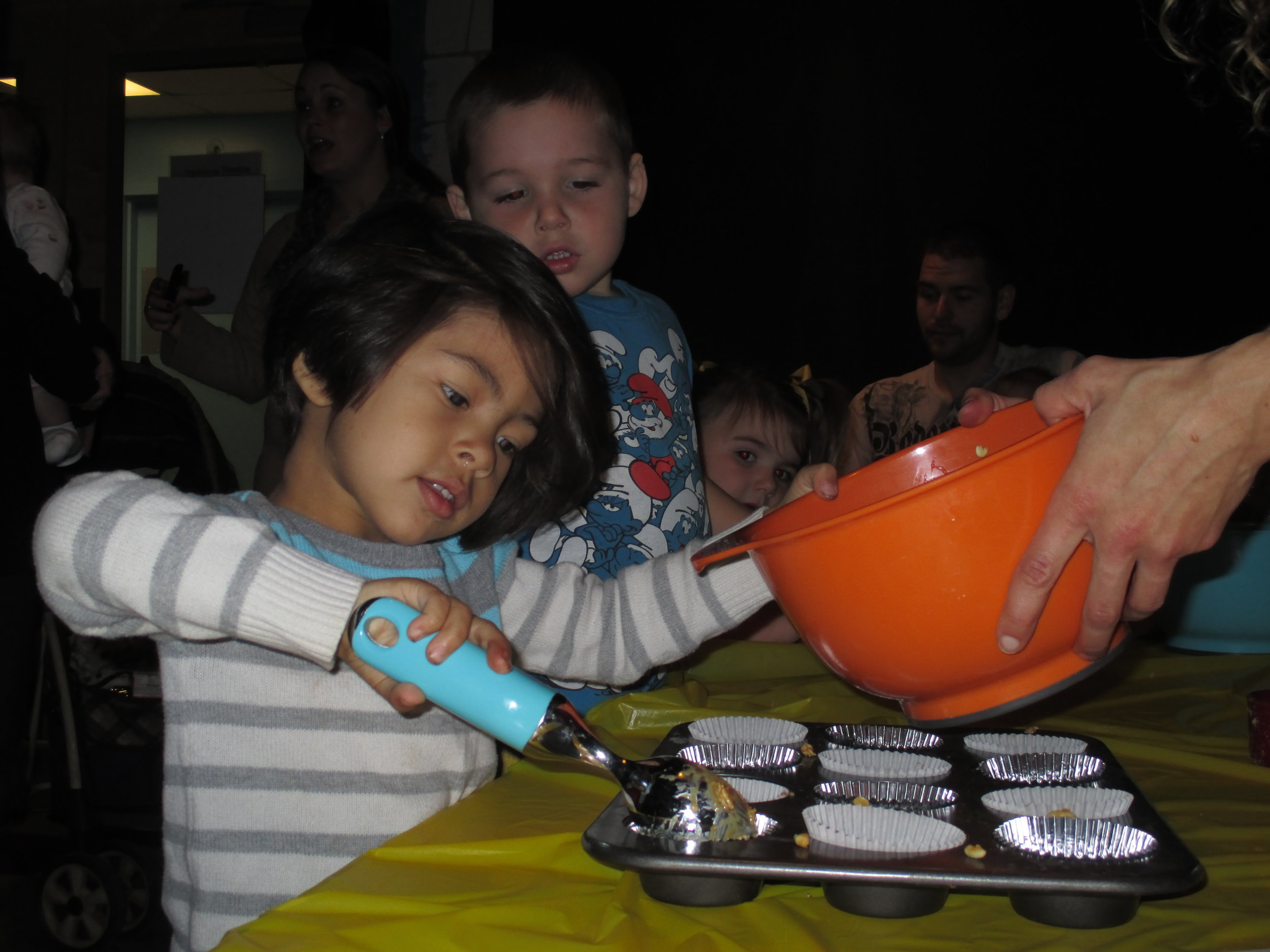 Camps- child scoops batter into cupcake tin.jpg