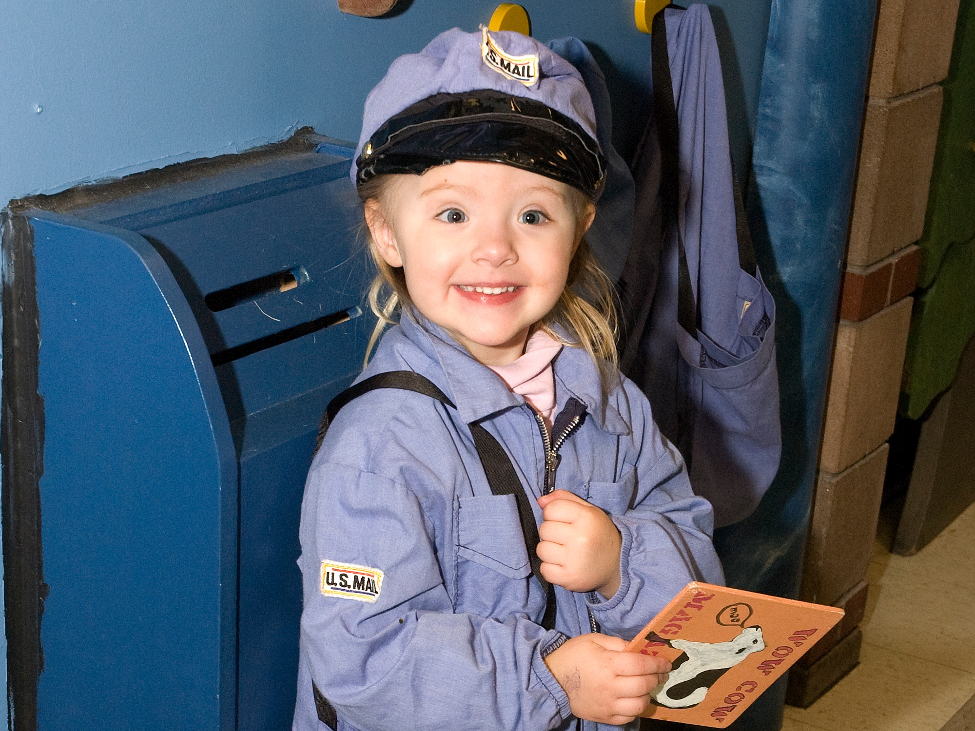 Child smiles in Post Office play uniform (Photo by Claudia Dricot).jpg