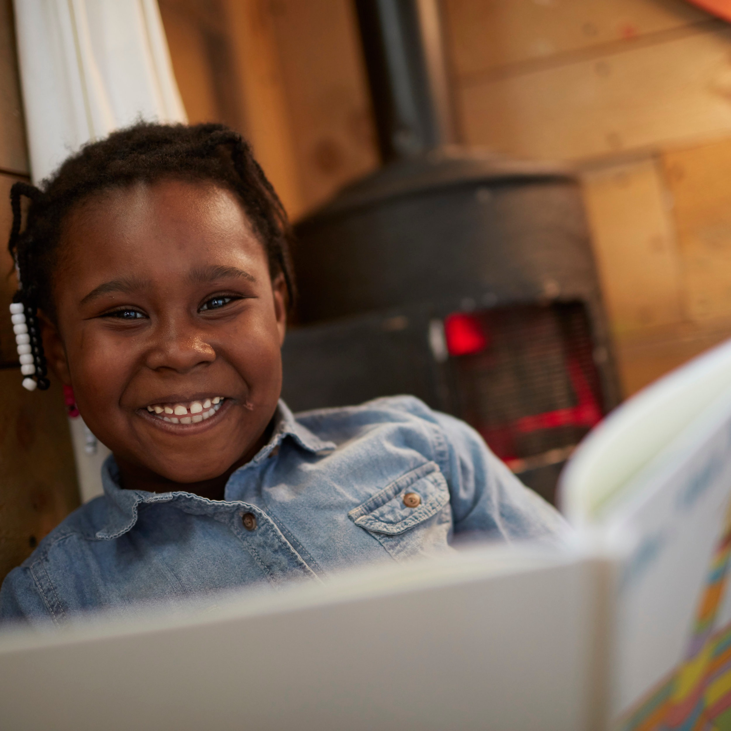 Child smiles while reading in Book Nook.jpg