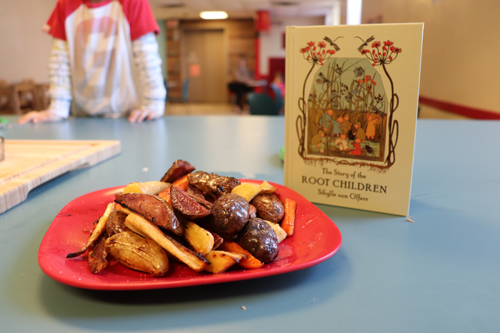 """Roasted roots meal in front of """"The Story of the Root Children"""" by Sibylle von Olfers."""