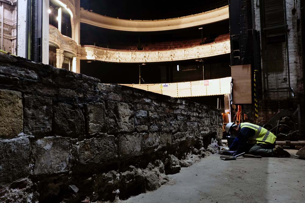 A post-medieval wall which formed the orginsl north external wall of the 1760s theatre and the view up into the dress circle..jpg