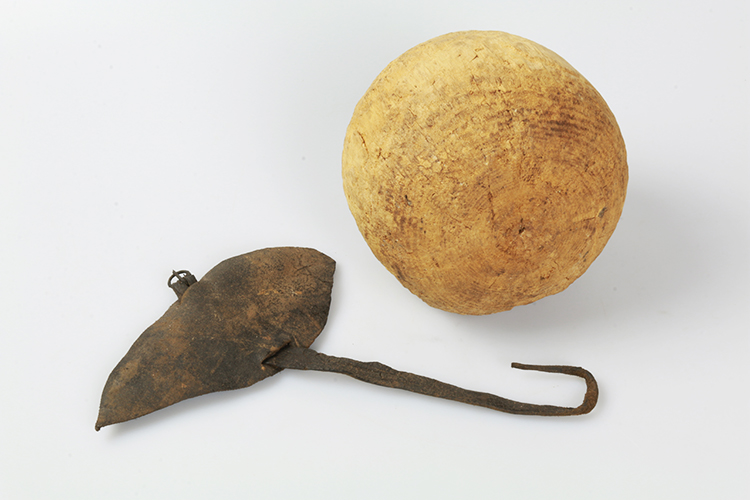 An archer's bracer made of leather protected the bowman's forearm when an arrow was loosed. The bowling ball is made of wood.