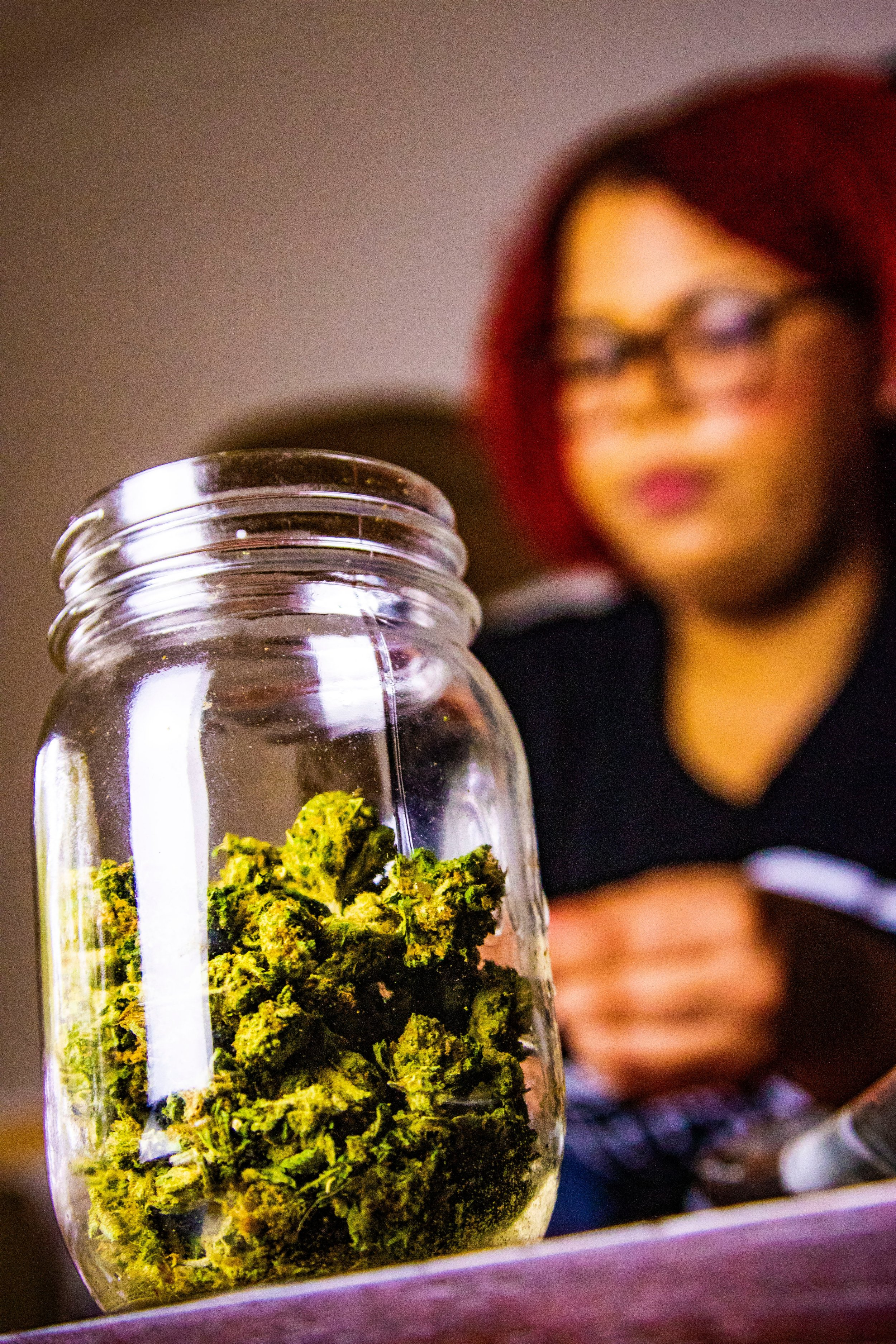 A jar of cannabis in the foreground with a woman in the background.