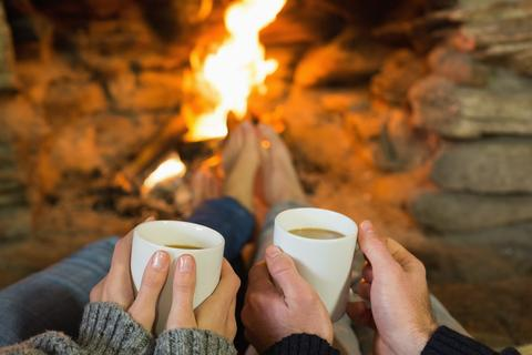 hands_holding_coffee_cups_romantic_fireplace_weekend_getaway_large.jpg
