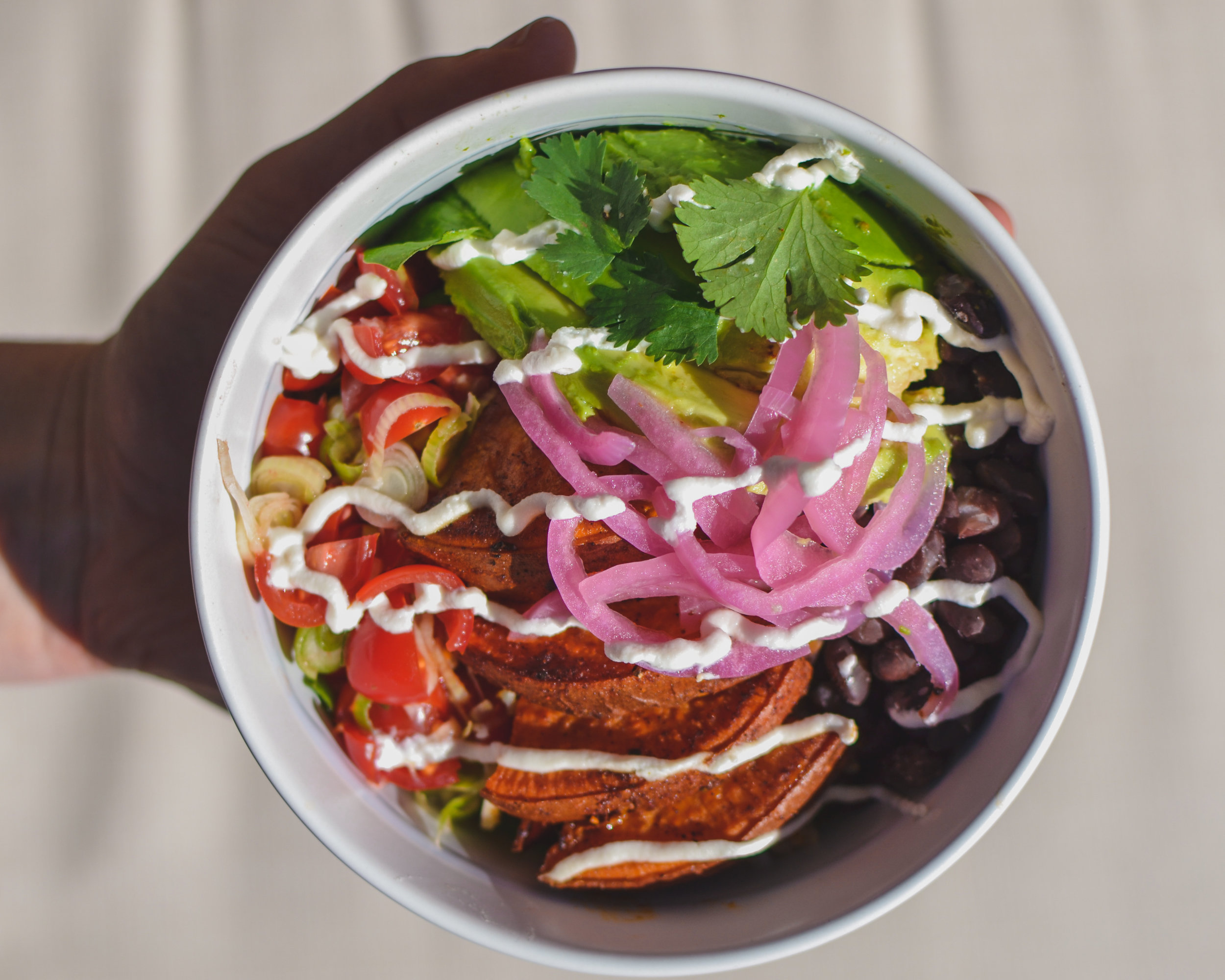 Baja Sweet Potato Burrito Bowl - Chili Roasted Sweet Potatoes, cumin black beans, arugula, brown rice, garlicky pico de Gallo, punchy pickled red onion, sliced avocado, labneh, Cilantro