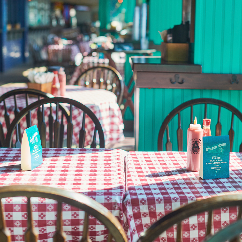 seating area for seafood restaurant, gingham tablecloth in Battery Park, FiDi 10004 – Oyster House at Pier A NYC.jpg