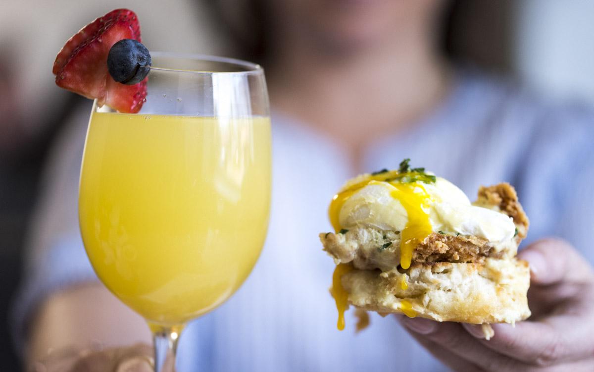close-up-eggsbenedict-overfriedchickenandbuscuit-mimosainwineglass-with0slicedstrawberryandblueberryonrim.jpg