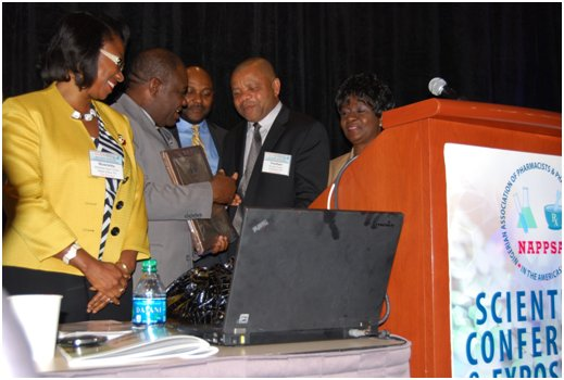 - The Hon. Minister of Power, Prof. Chinedu Nebo receiving a plaque of appreciation from NAPPSA President Nnodum Iheme, R.Ph., while the Program Committee Chair, Anthony C. Ikeme, Ph.D. (bk-ctr), Moderator, Dr. Mrs. Henrietta Ukwu (left) look on.