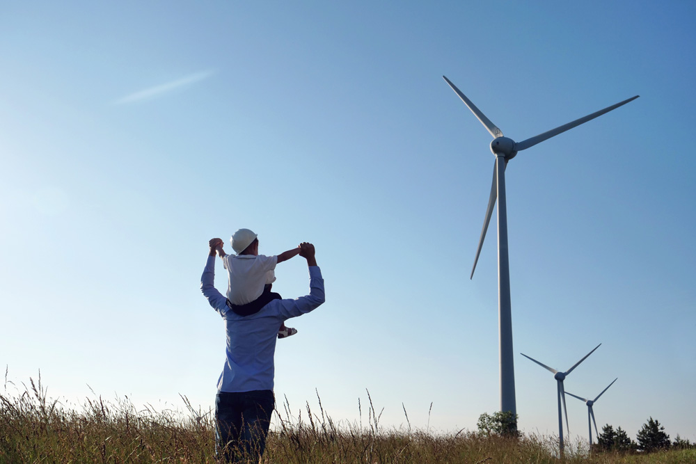 Man carrying child by wind turbines