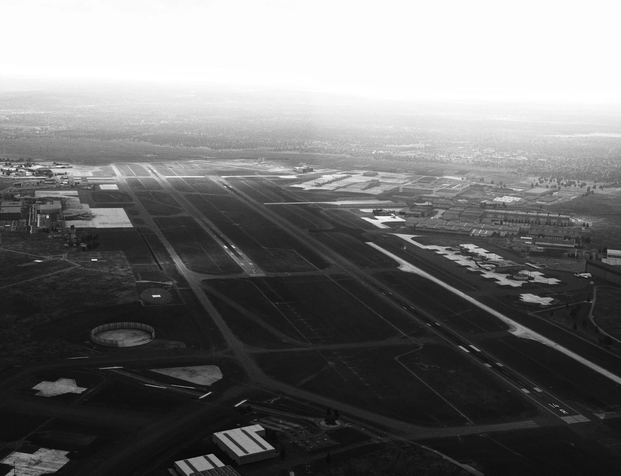 A synthetic image of Toulouse-Blagnac airport, as generated in X-Plane with custom post-processing shaders, displaying backlit atmospheric effects and broken cloud cover over the airport.