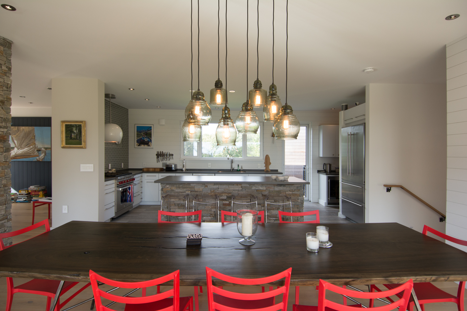 Open plan dining room and kitchen with red chairs and pendant lighting