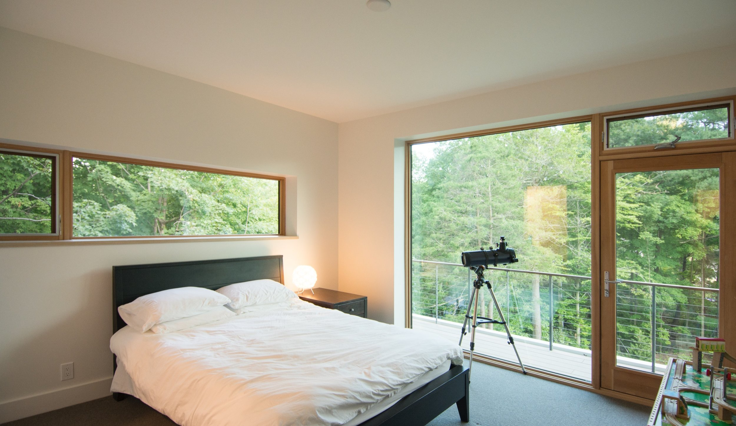 Bedroom with balcony and views into trees