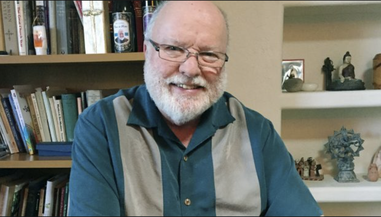 Fr. Richard Rohr, with shelves of Christian/Buddhist/Hindu books and figures.