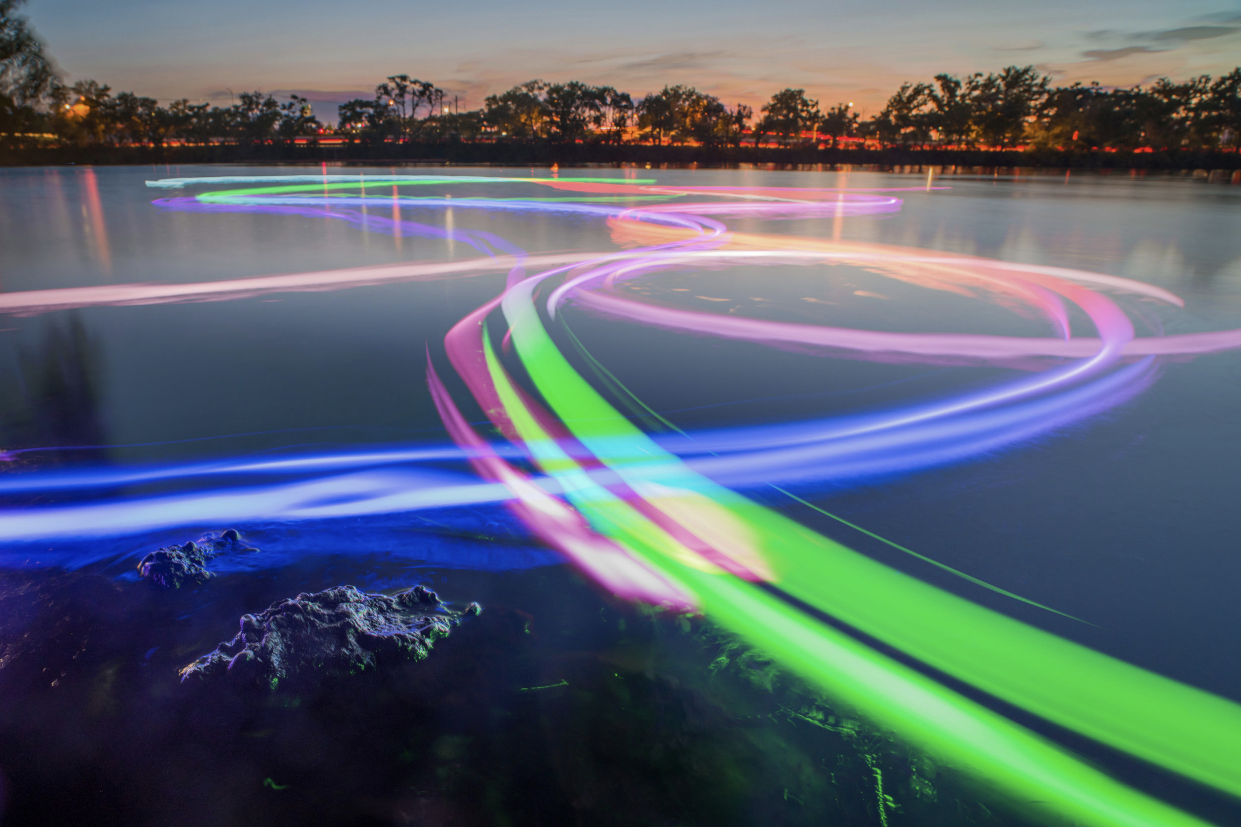 A composite long exposure image captures the light trails drawn on the river by many community members throughout the evening at Magazine Beach   ArtBoat: Magazine Beach, 2018 // project: Laura Perovich // photo: Jorge Valdez