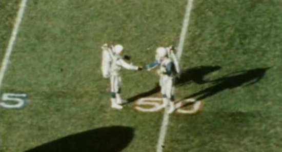 """Two jetpack pilots shake hands at the 50 yard line after landing (Super Bowl I film """"The Spectacle of a Sport"""")"""