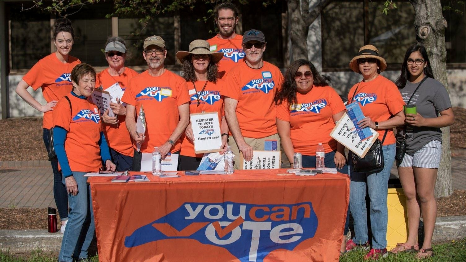 Some of our great volunteers wearing the orange You Can Vote shirts stand in front of a table with a You Can Vote banner and a variety of pamphlets and clipboards.