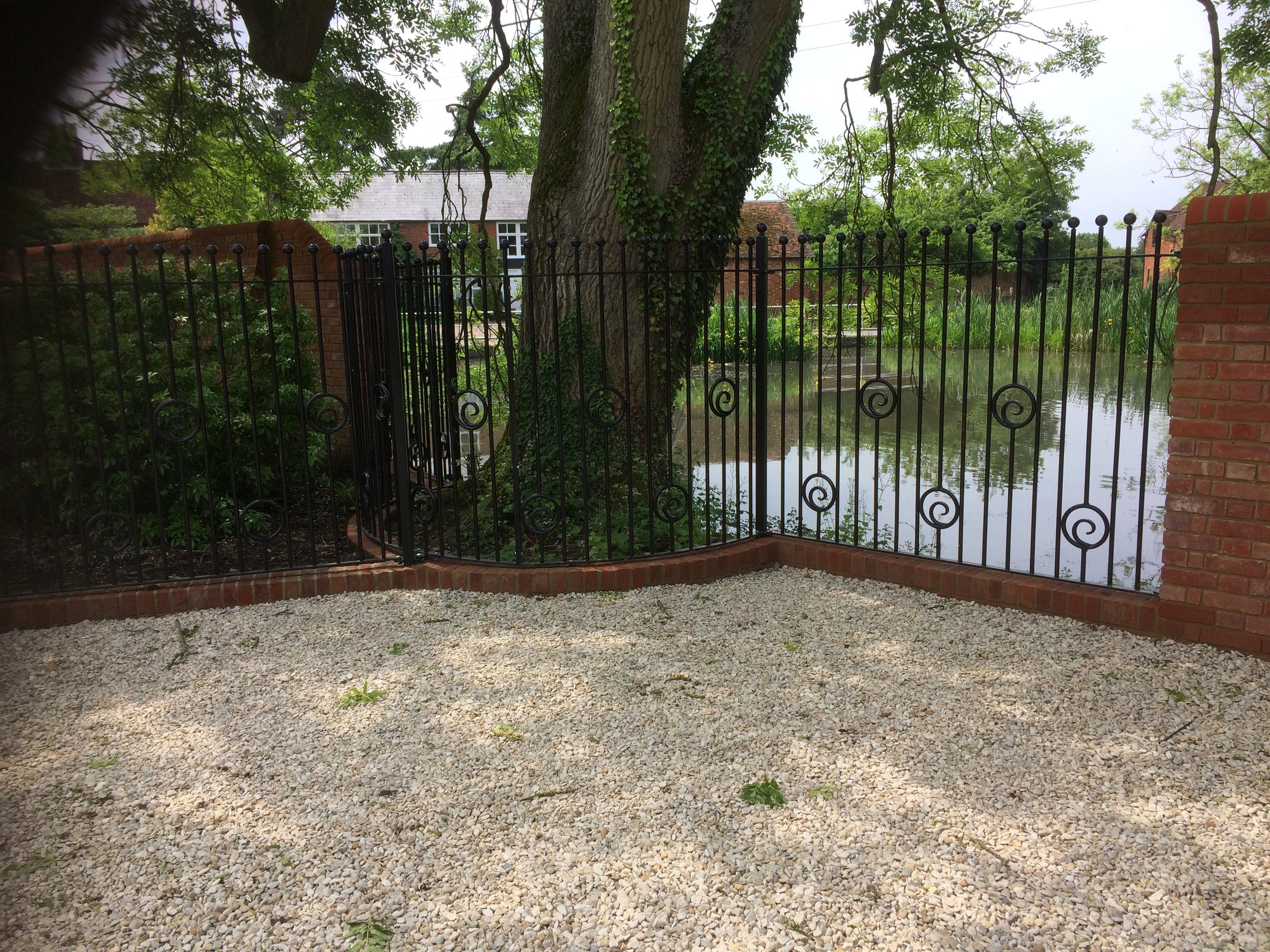 Some of the extensive work carried out for a large Buckinghamshire house, railings to the client's design curving around a tree bordering the village pond.