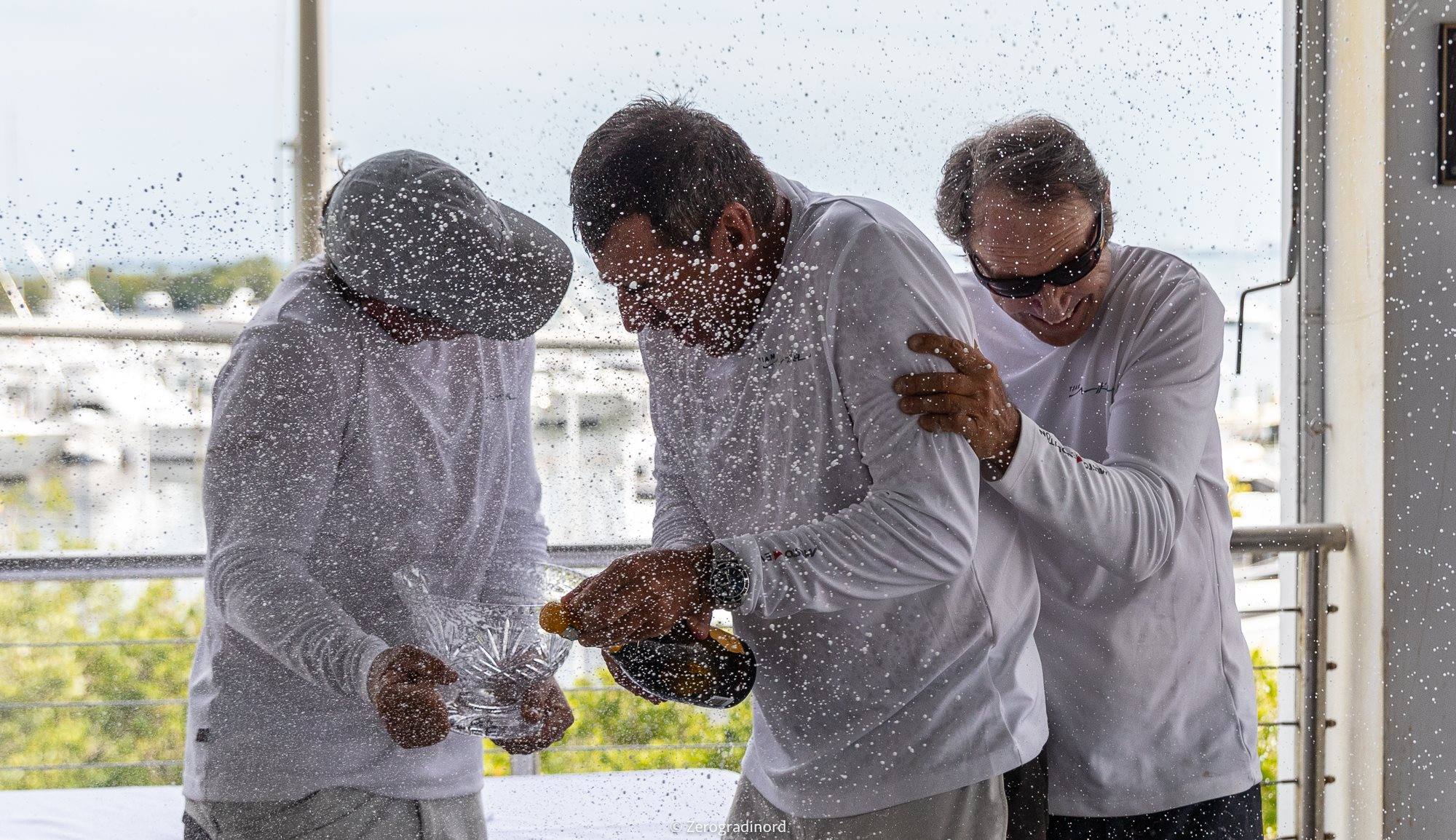 NIKA  Champagne celebrations with Vladimir Prosikhin (helm), Morgan Reeser and Charlie Smythe. Photo by Zerogradinord.