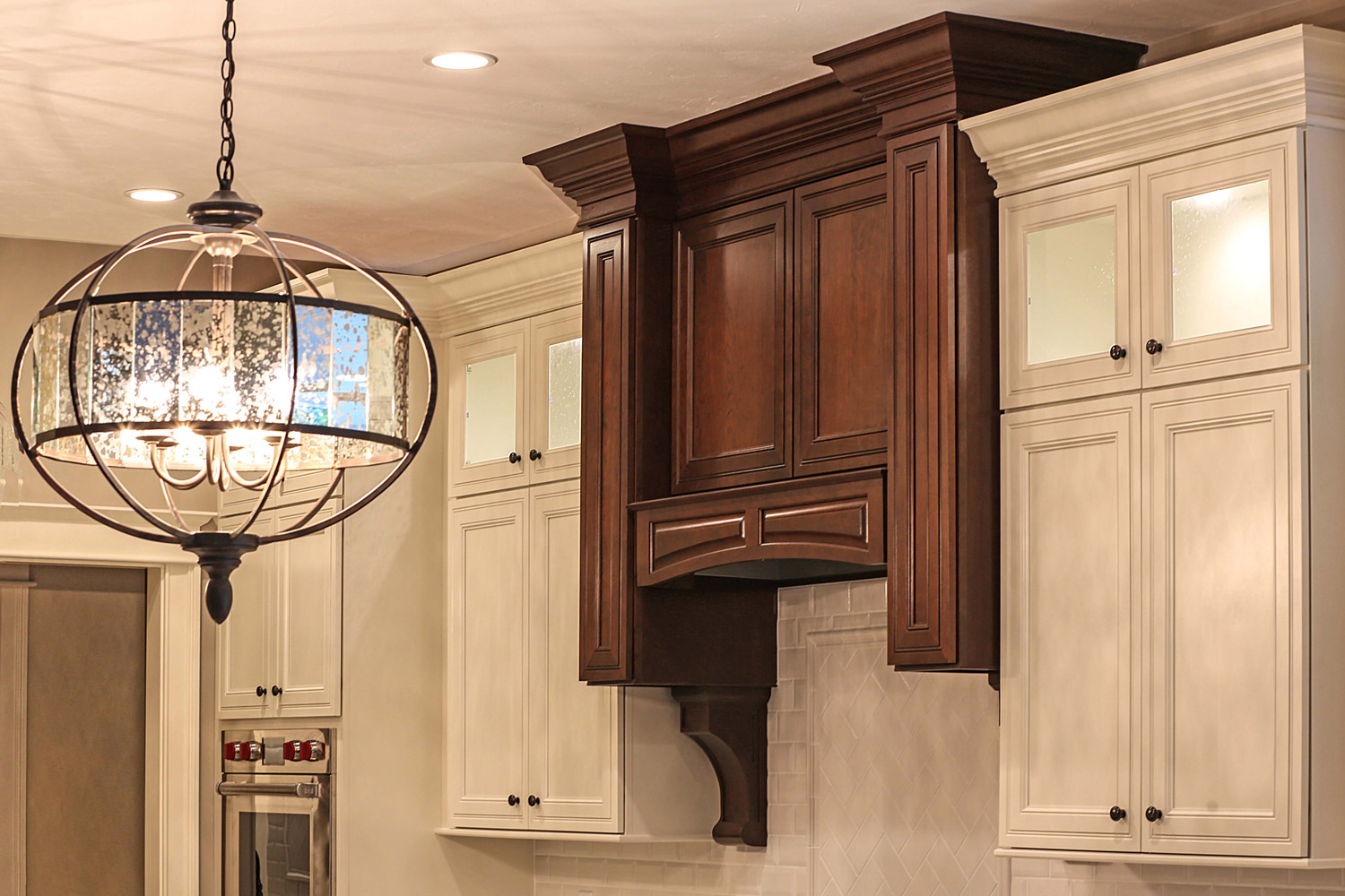 Off-white cabinets contrast range hood with corbels in Espresso finish.
