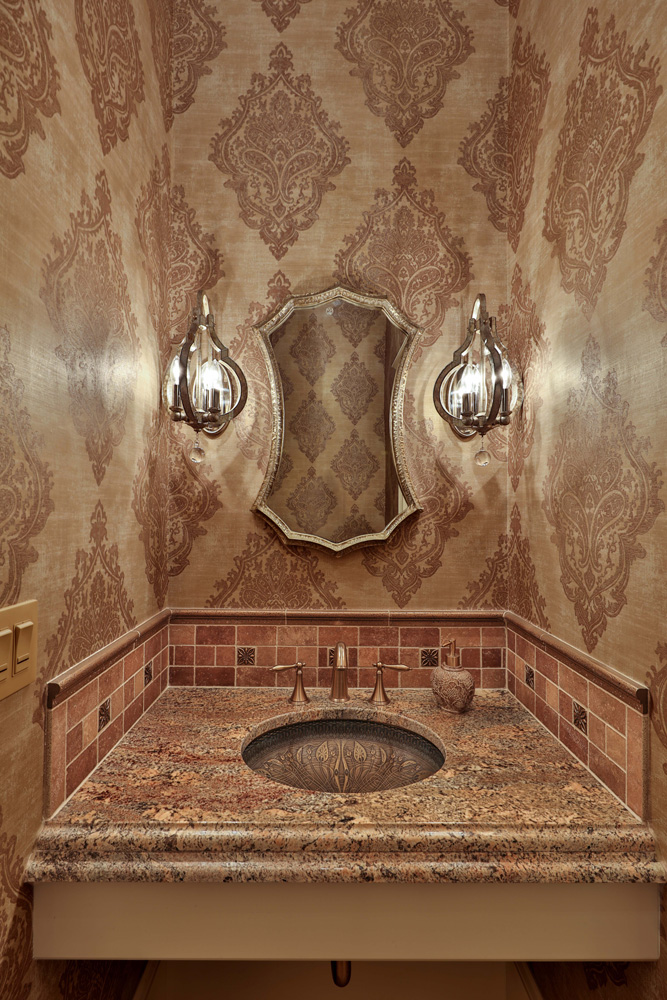 Bathroom design with wallpaper, sconce lighting and intricate bottom mount sink.