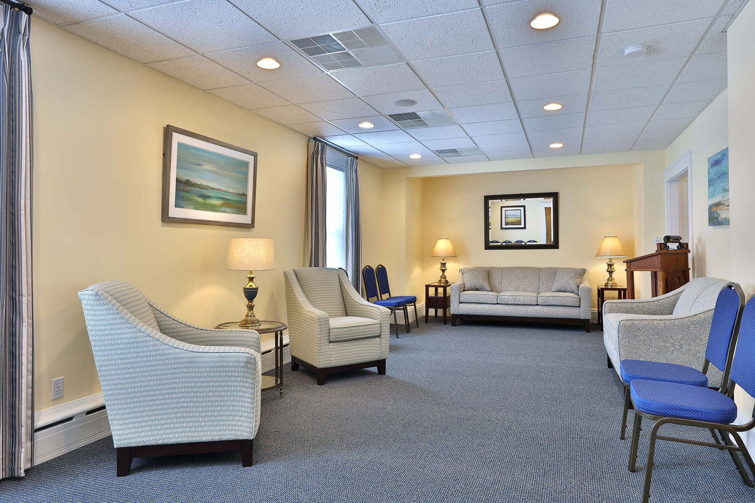 Upholstered seating groupings in French blue and gold speck commercial carpet.
