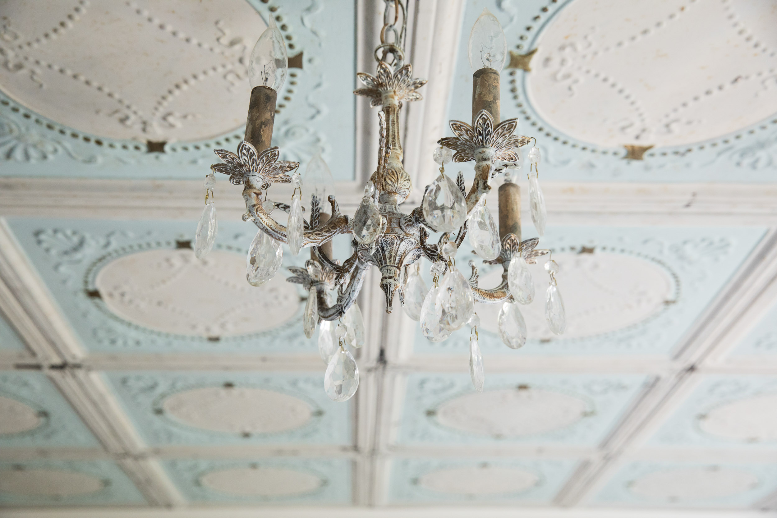 Salvaged blue and white tin ceiling tiles and an antique crystal and brass chandelier.