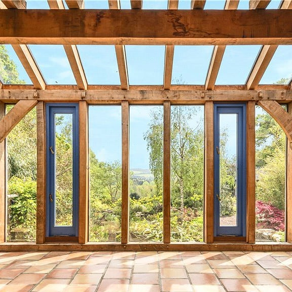 Oak framed conservatory VIEWS!  This RJA designed barn conversion and extension is for sale in Lyme Regis!  Contact @symondsandsampson for details!  #forsale #conservatory #oakframe #bluewindows #oakframing #timberframehouse #extension #estateagents #property #propertyforsale #garden #lymeregis #dorset #retreat #fixedglazing #timberframe #architecture #roderickjames #architect #roderickjamesarchitects