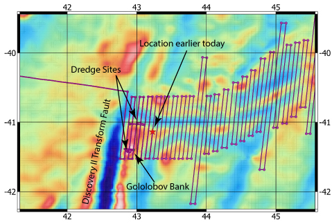 """Our location earlier today (red star). We've completed all of the multi beam lines to the west of the """"star"""" and the horizontal ship tracks show where we went dredging. The """"topography"""" is from satellite derived gravity."""