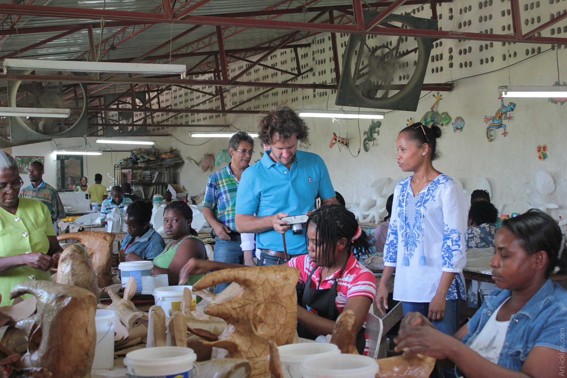 Blake, founder of TOMS Shoes, taking pictures of artisans handcrafting a faux taxidermy rhino head in paper mache.