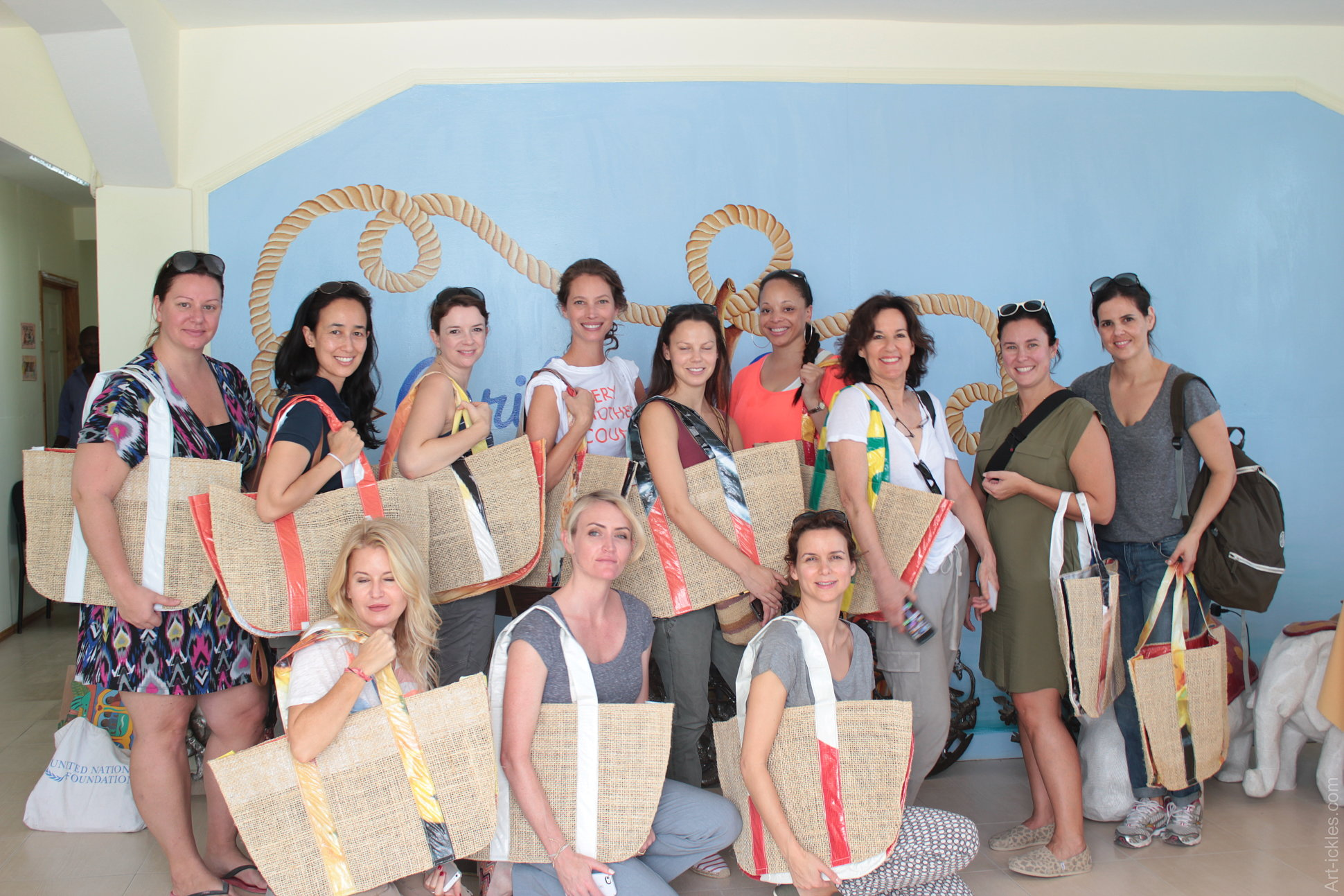 """Visit by """"Every Mother Counts"""" with supermodel Christy Turlington (center with the Every Mother Counts T-shirt) and Dwell Studio founder Christiane Lemieux (1st left on the front row). They are showcasing a beach bag created by Caribbean Craft in locally harvested sisal and reused billboard plastic."""