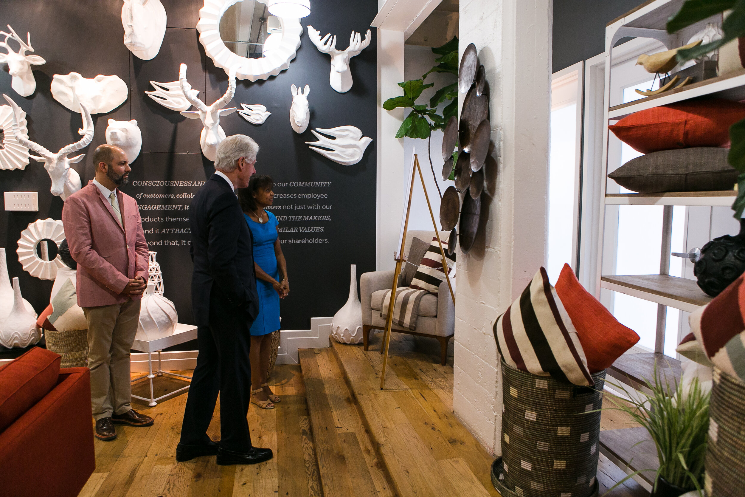 Former US President Bill Clinton views the home decor made by Caribbean Craft for West Elm