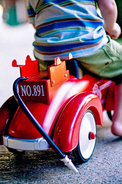 Young boy riding toy car