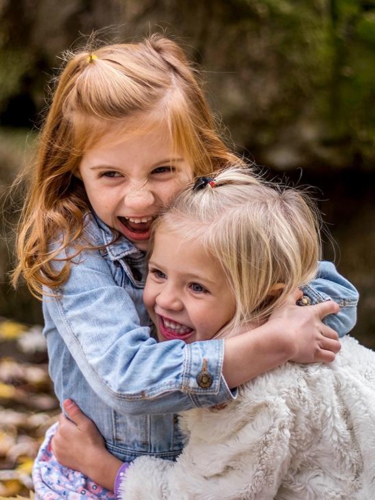 Two young girls outside wearing coats