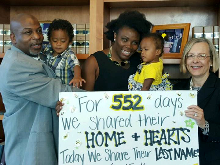 """Foster family holding poster that reads """"For 552 days we shared their home and hearts. Today we share their last name!"""""""