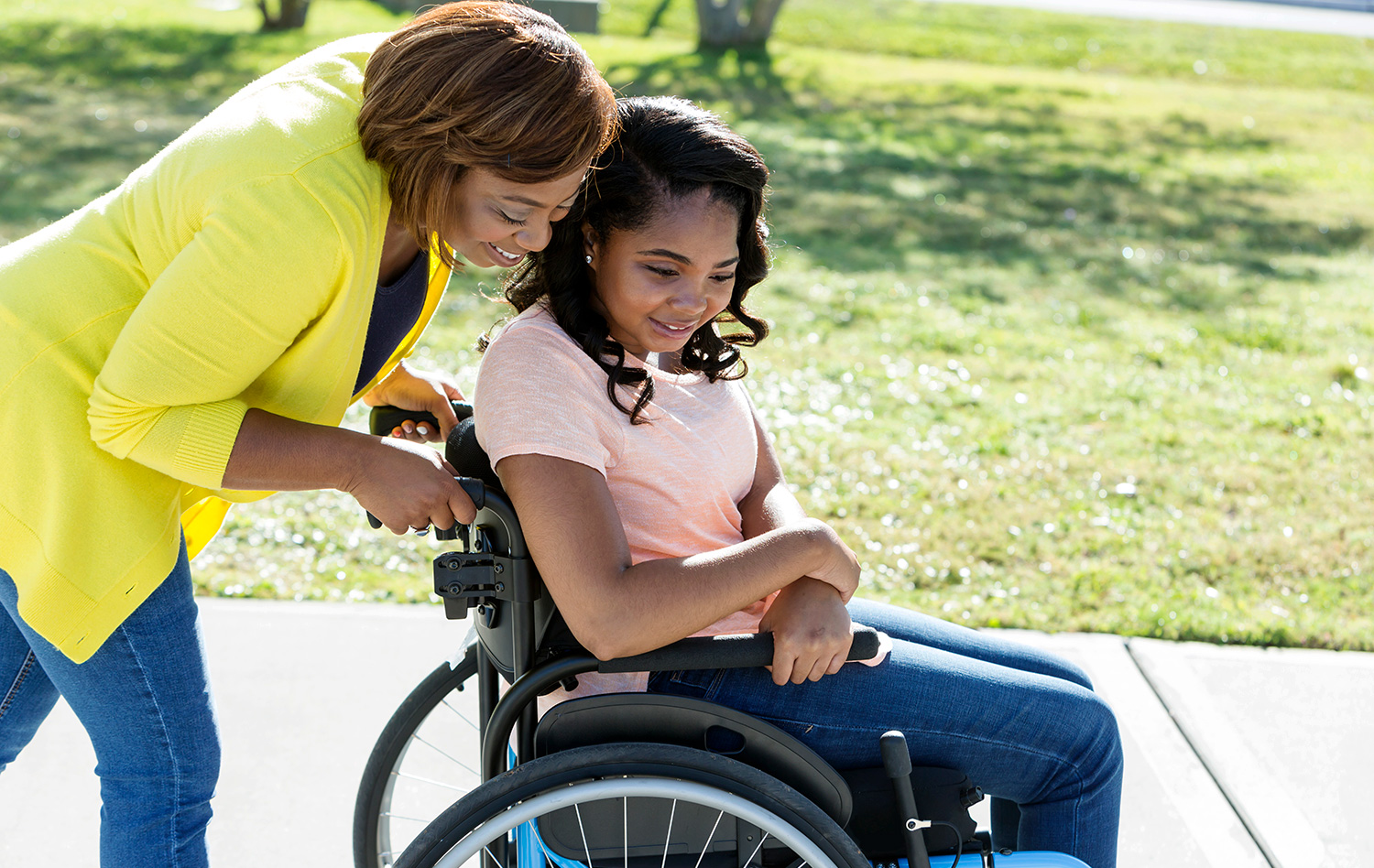 Woman pushes girl in a wheelchair.