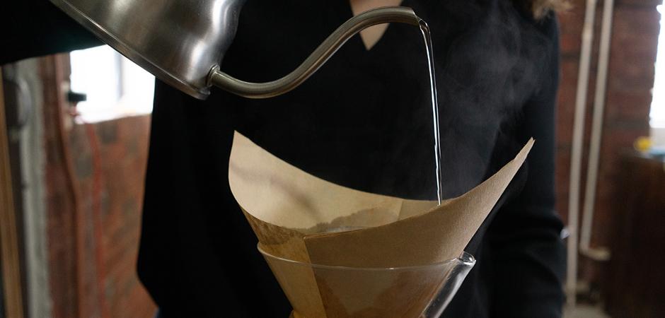 PASO 01  Coloca tu filtro para Chemex de manera cónica en tu Método Manual. Vierte un poco de agua caliente sobre el filtro de papel para limpiar y quitar cualquier cualquier residuo de papel, y evitar contaminar el sabor de tu taza final.