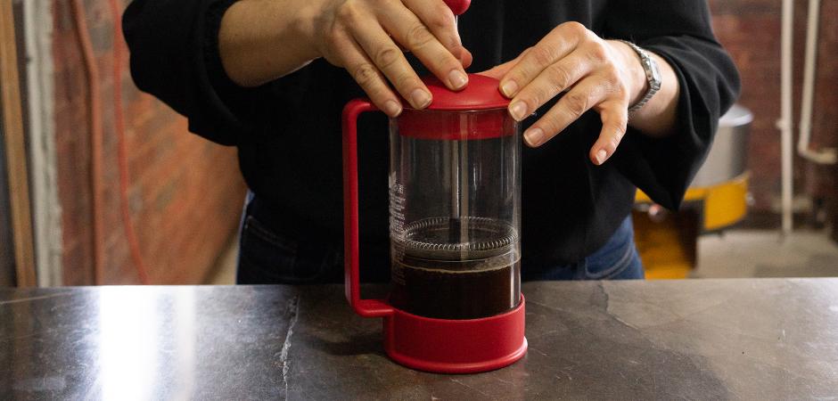 PASO 04  Coloca la tapa de tu prensa y espera 3 minutos más para bajar el émbolo o pistón de tu prensa para separar el grano de café de la infusión.