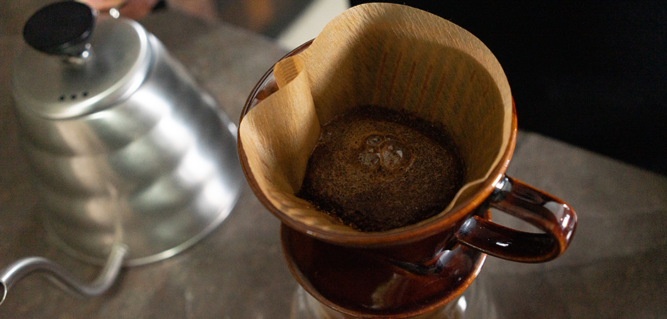"""PASO 03  Pon suficiente cantidad de agua sobre el café molido para humedecerlo. Deja de verter agua una vez húmedo tu café molido. Lo que ocurrirá con el grano de café es el """"Bloom"""", a este proceso se le llama a los movimientos burbujeantes que se observan en el café y esto ayuda a desgasificarlo y por ende, tendrás una taza más limpia. Esto toma alrededor de 40 segundos."""