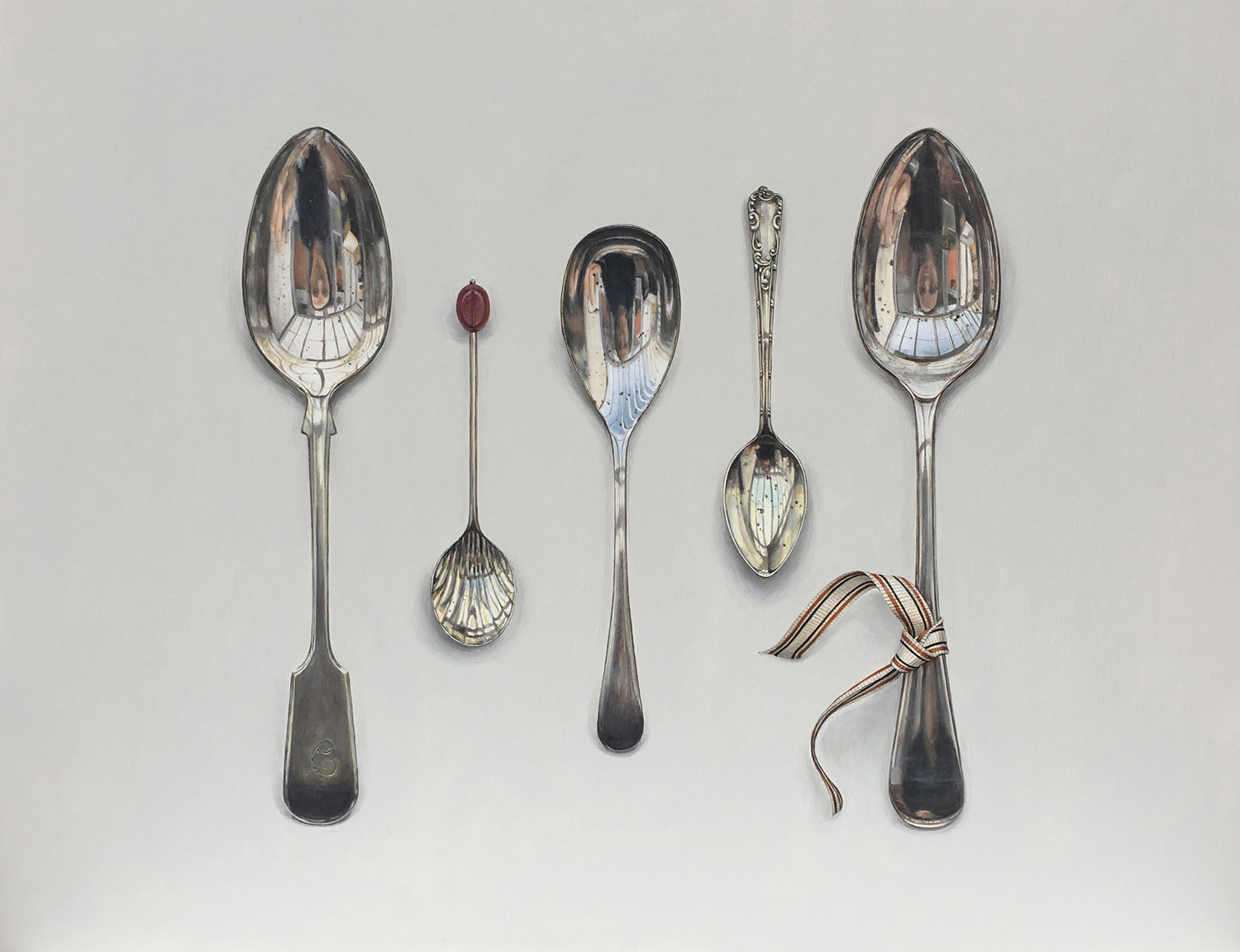 arranged spoons with striped ribbon