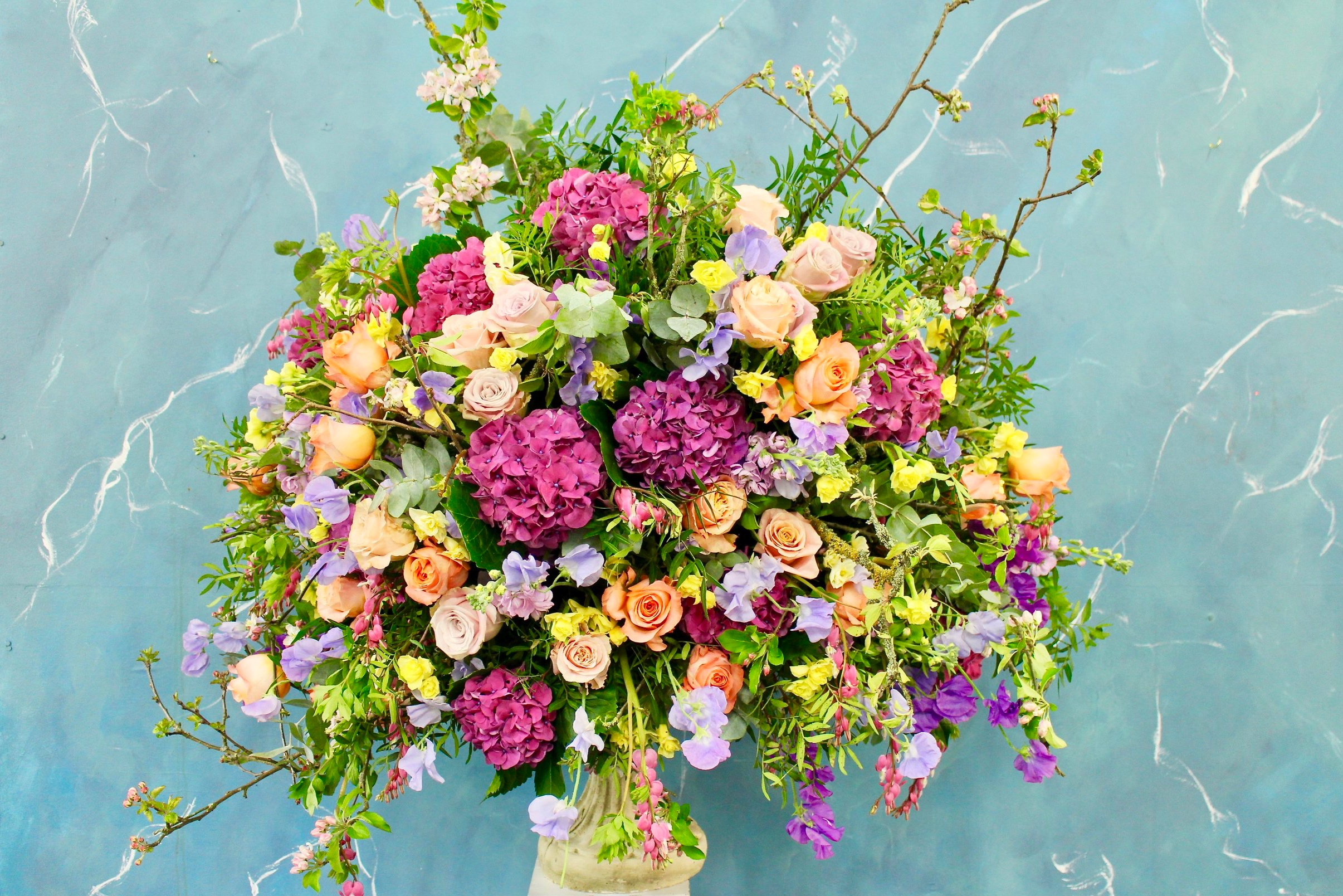 A spring urn filled with hydrangea, faith roses, apple blossom, sweet peas, daffodils, and an abundance of textured foliage