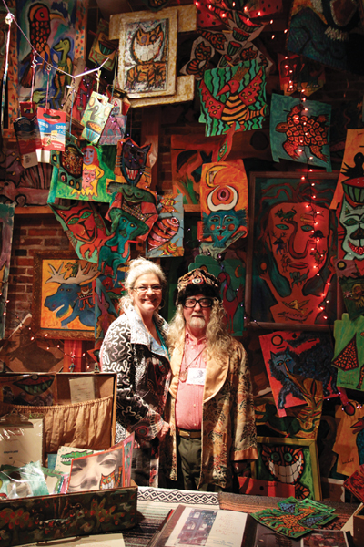 "Alison Spiesman and Brian Dowdall smile in front of Dowdall's ""Wall of Color"" painting at Bazaart.  Photo from Baltimore Style magazine."