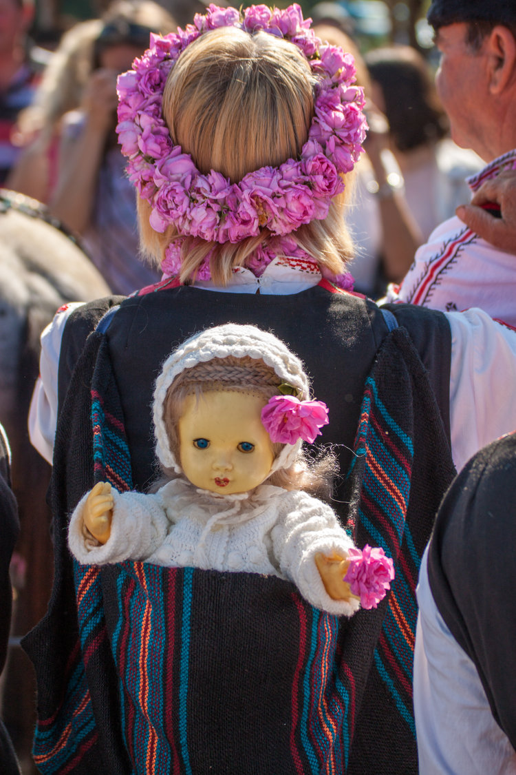 """The woman in this picture has a doll in a traditional special bag, called """"tsedilka"""" - it was once used for carrying a baby on one's back.    Gorno Cherkovishte, Bulgaria - May 31, 2015: Annual Rose picking ritual in Gorno Izvorovo village. People from the village dressed up in a traditional folklore costumes sing and harvest the Bulgarian roses. Source: iStock by Getty Images"""