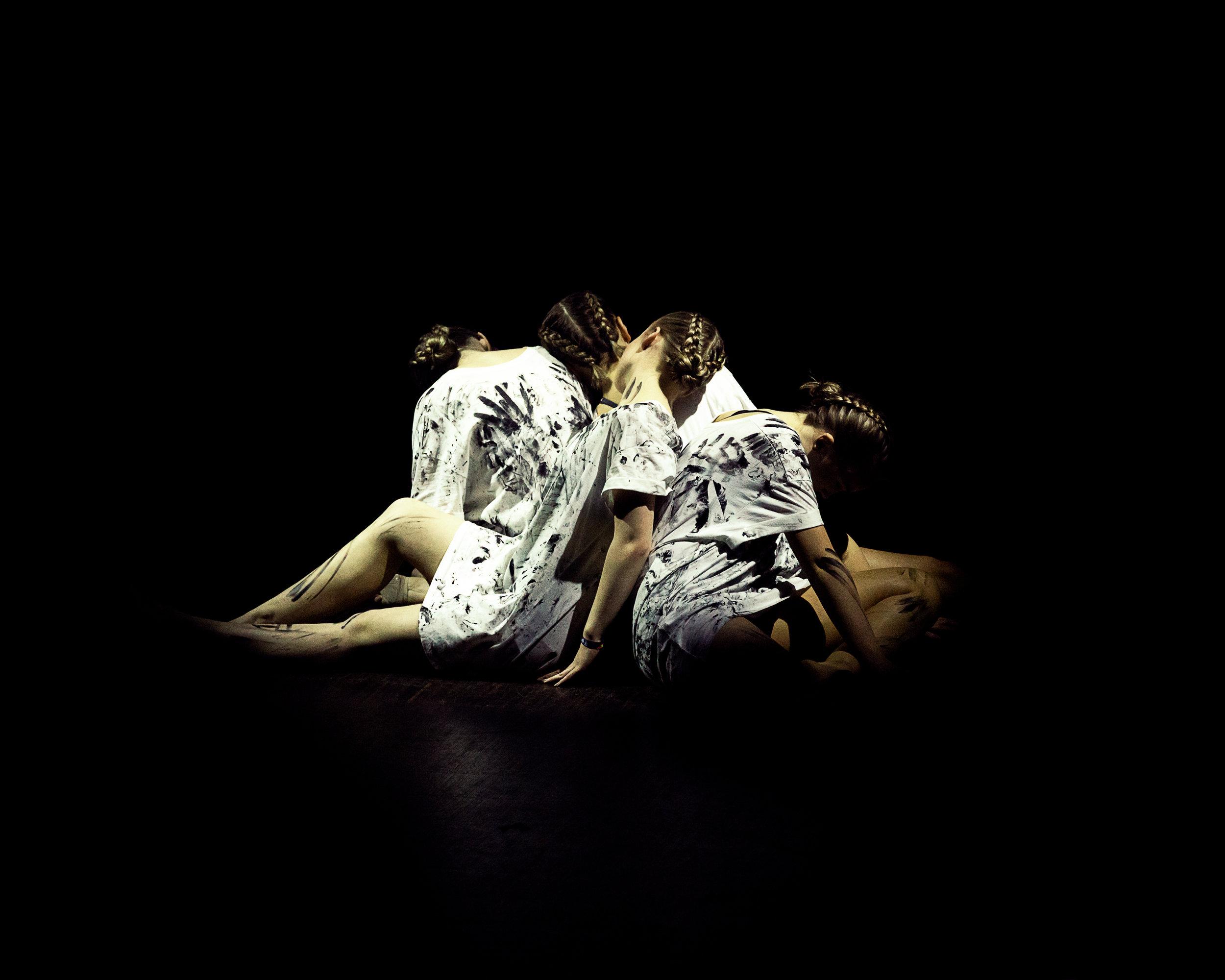 Dansere som sitter på scenegulvet. hvite skjorter med et lys over dem. mørkt men lyst i midten. portrett av dansere. event og scene på en festival fotografi.