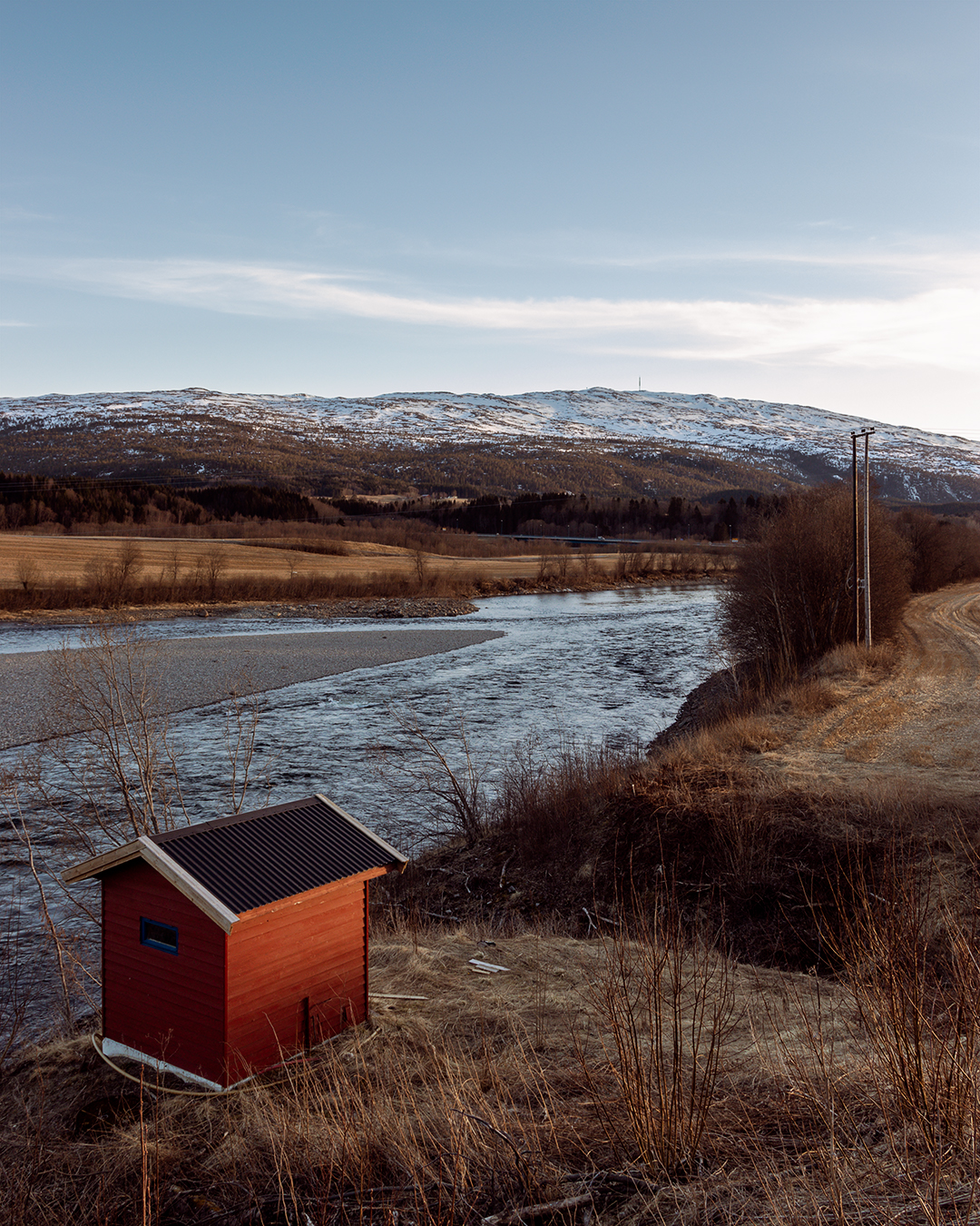 Rødt hus ved en elv med fjell i bakgrunne,. landskap på en klar dag. solnedgang. rødt blått. jorder og gård-
