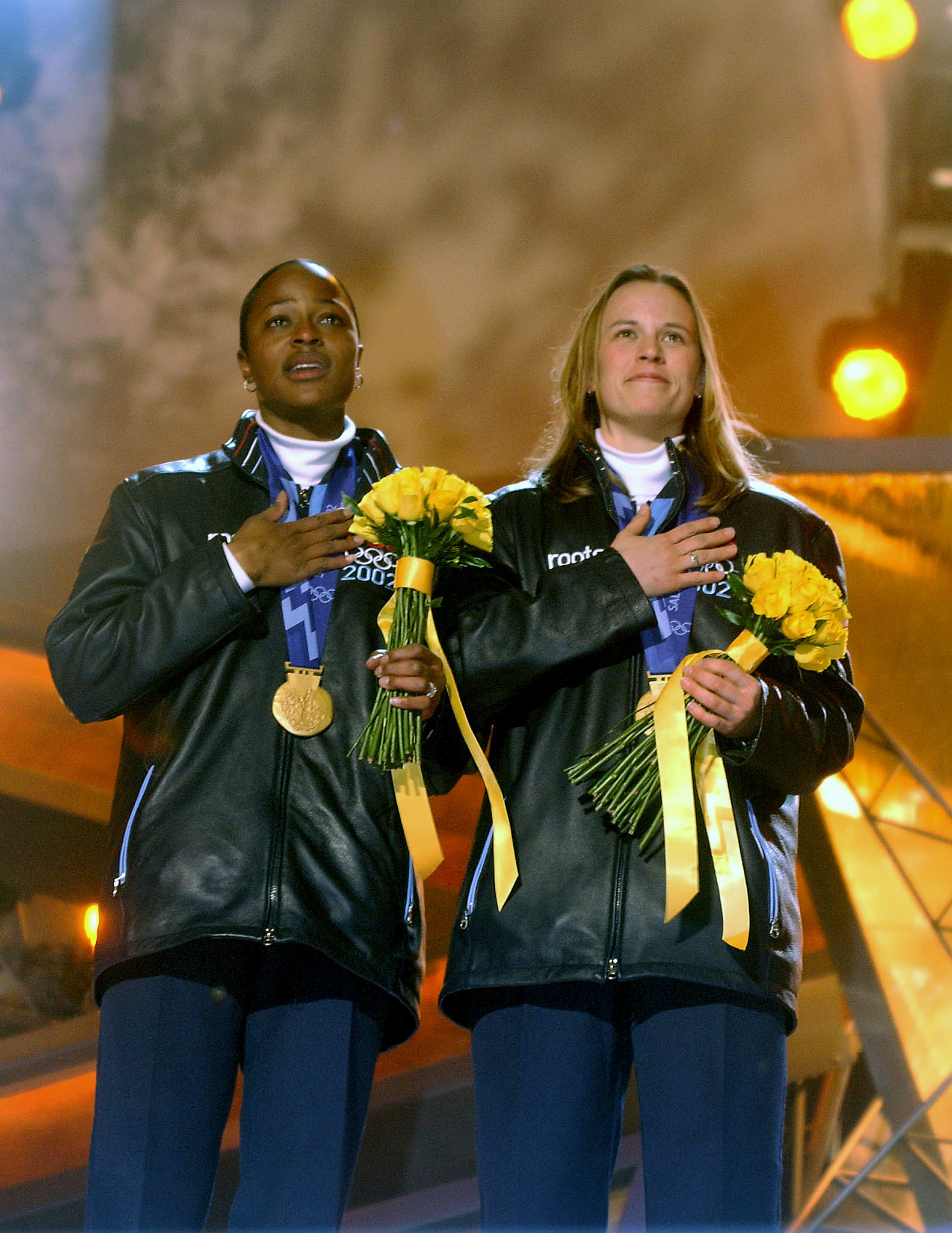 Flowers and Bakken with gold medals during the playing of the US National Anthem. Flowers becomes the first African American to win a gold in the Winter Olympics.