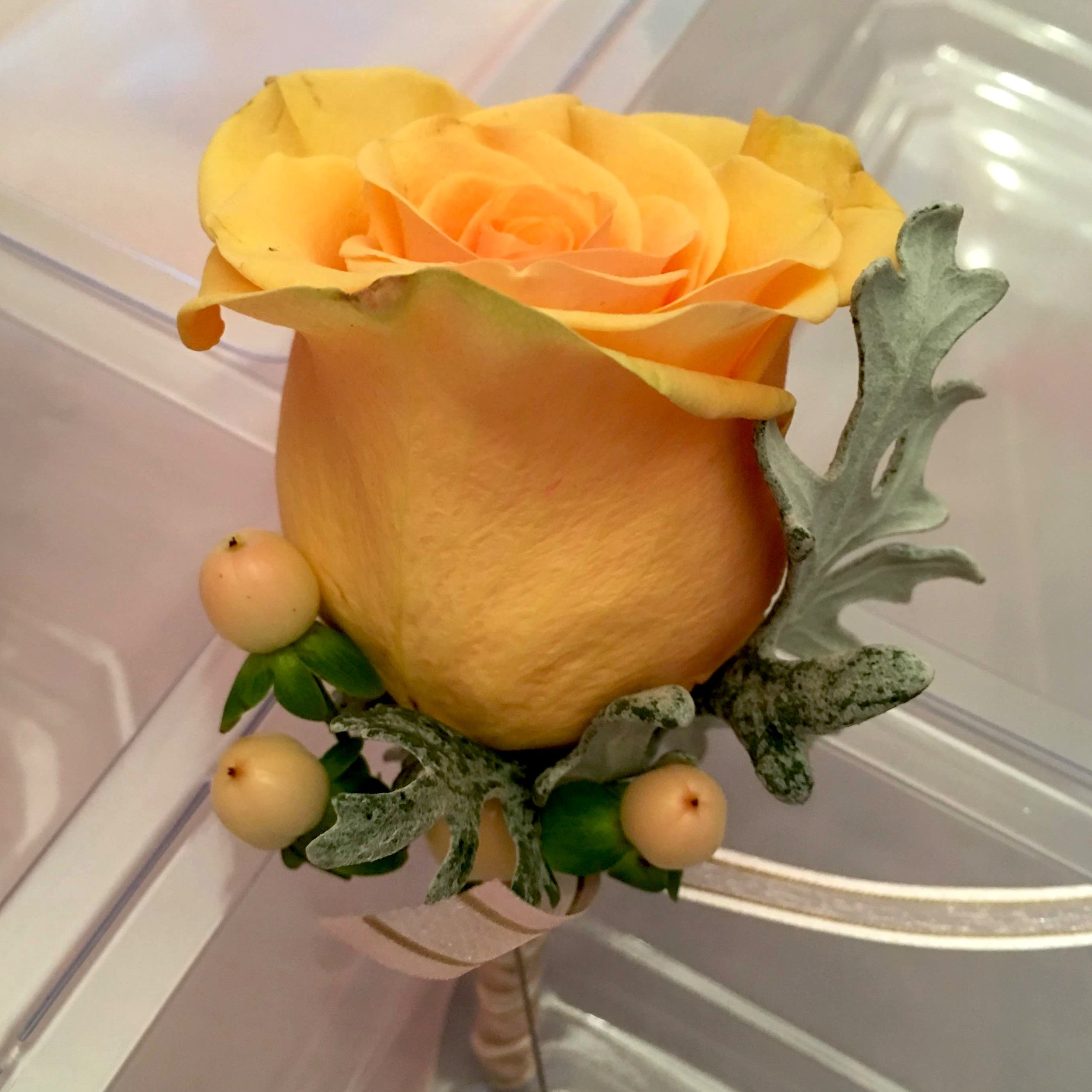 - A simple color palette is all that's needed to highlight a boutonniere sometimes. Peach and green are a great combination, and it you look closely, those leaves are to die for!