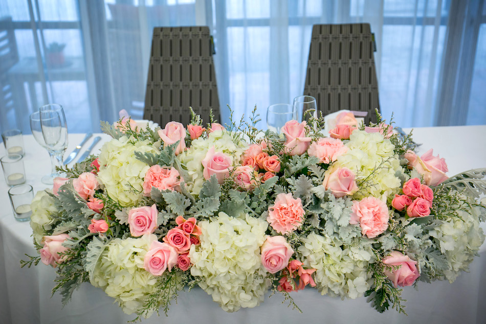 - One of the most cost effective ways to create a centerpiece for the sweetheart table is to gather all the bride and bridesmaids bouquets. We love how these bouquets come together to create a soft and romantic centerpiece for the sweetheart table.